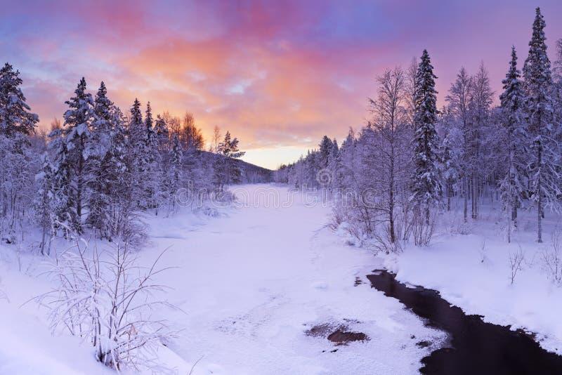 Soluppgång över en flod i vinter nära Levi, finlandssvenska Lapland royaltyfri foto
