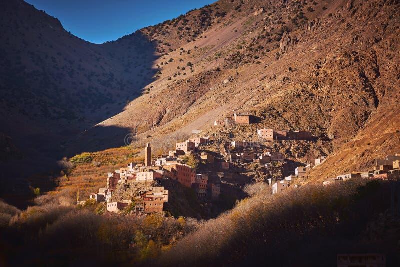 Soluppgång över en traditionell by i höga kartbokberg royaltyfri fotografi