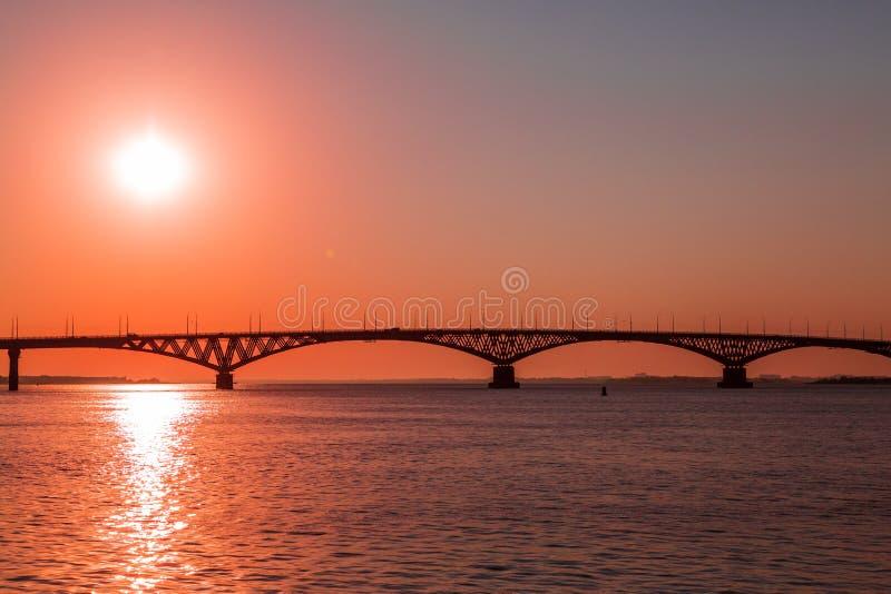 Soluppgång över en vägbro över Volgaet River mellan städerna av Saratov och Engels, Ryssland fotografering för bildbyråer