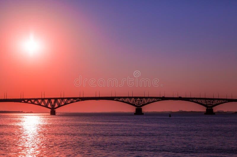 Soluppgång över en vägbro över Volgaet River mellan städerna av Saratov och Engels, Ryssland royaltyfria foton