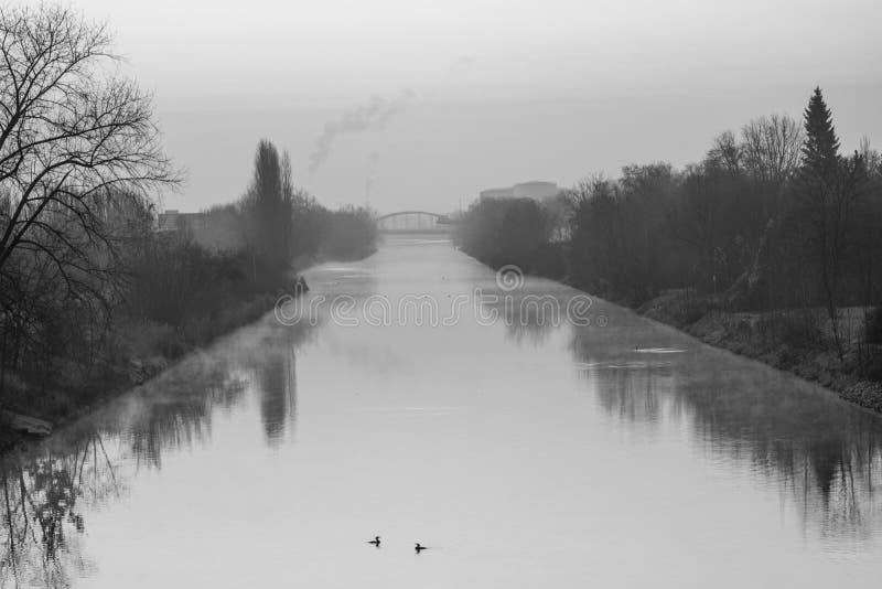 Soluppgång över en vattenväg i Berlin på en dimmig morgon med sikt till en bro i bakgrund - svartvitt fotografi arkivbild
