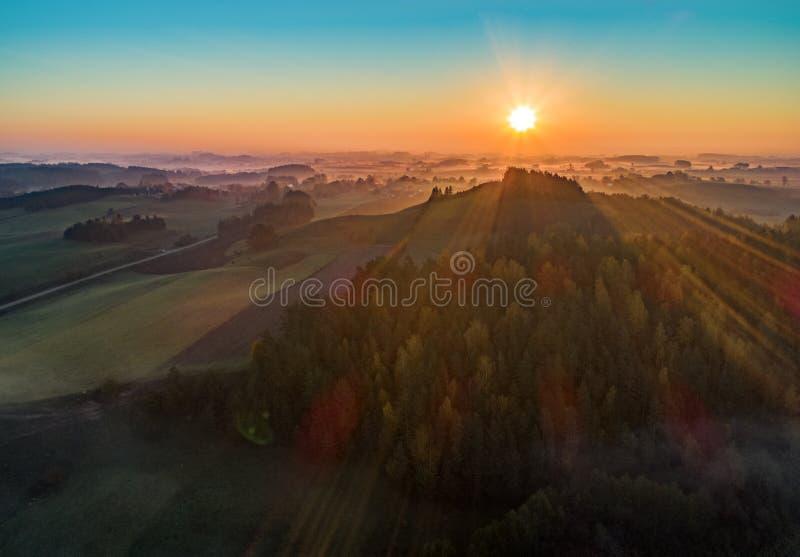 Soluppgång över ett berg och en skog - flygbild fotografering för bildbyråer