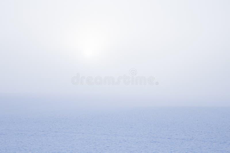 Soluppgång över fält med snö och dimma royaltyfri bild