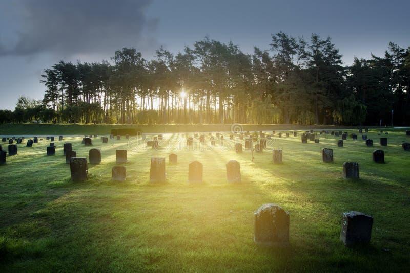 Soluppgång över gravstenar arkivfoton