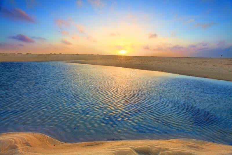 Soluppgång över guld- sander och azurvatten royaltyfria bilder