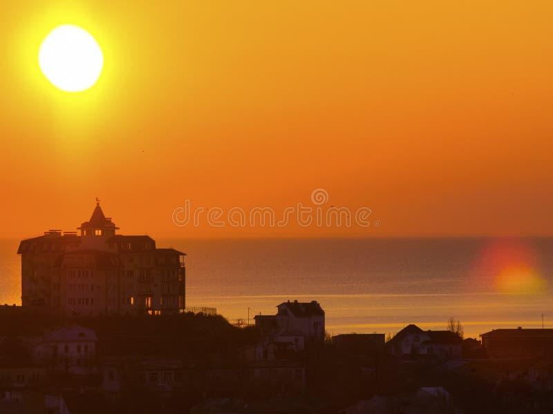 Soluppgång över havet och huset på berget royaltyfri bild