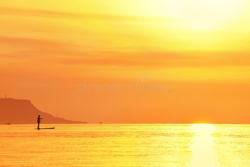 Soluppgång över havs- och folkSUPEN står paddla upp royaltyfria bilder