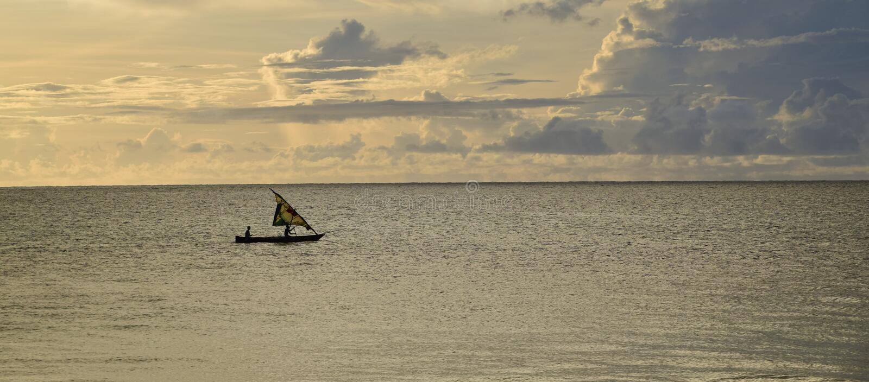 Soluppgång över Indiska oceanen Segelbåt under guling, molnig himmel royaltyfri bild