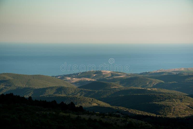 Soluppgång över kullar och havet royaltyfri fotografi