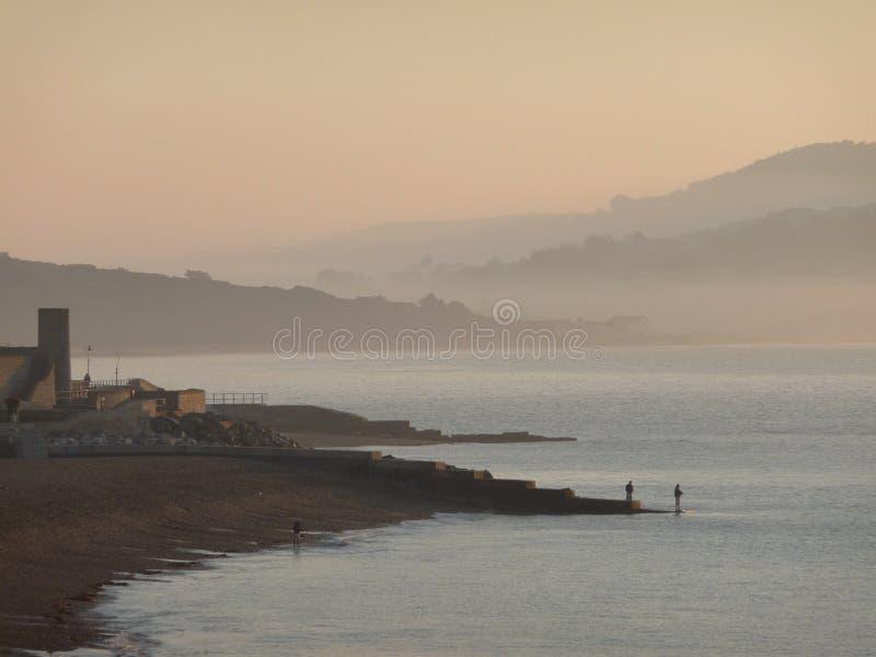Soluppgång över Lyme Regis, Dorset royaltyfri bild