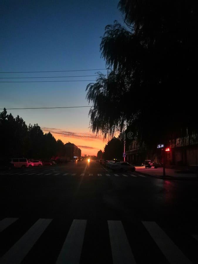 Soluppgång av en liten stad på slutet av vägen royaltyfri foto