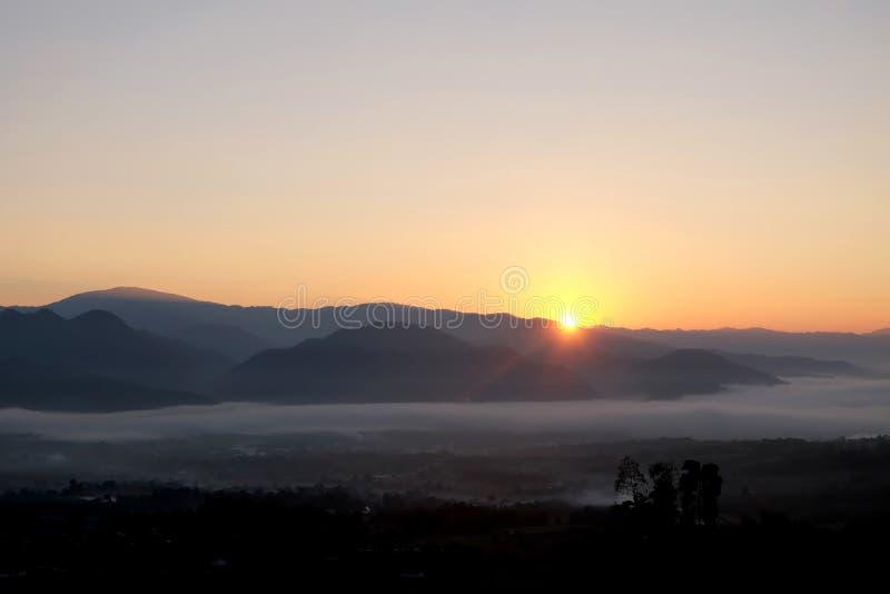 Soluppgång bak berget i morgonen med storartat mistlandskap i vintersäsong arkivfoton