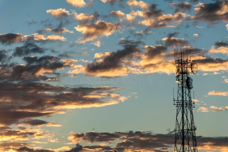 Soluppg?ng bak ett kommunikationstorn f?r radio- och tvradiouts?ndning arkivbild