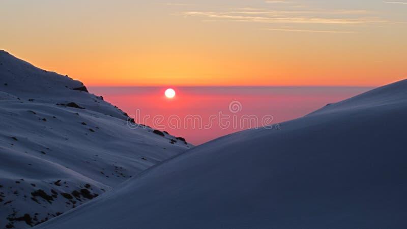 Soluppgång bak snön arkivbild