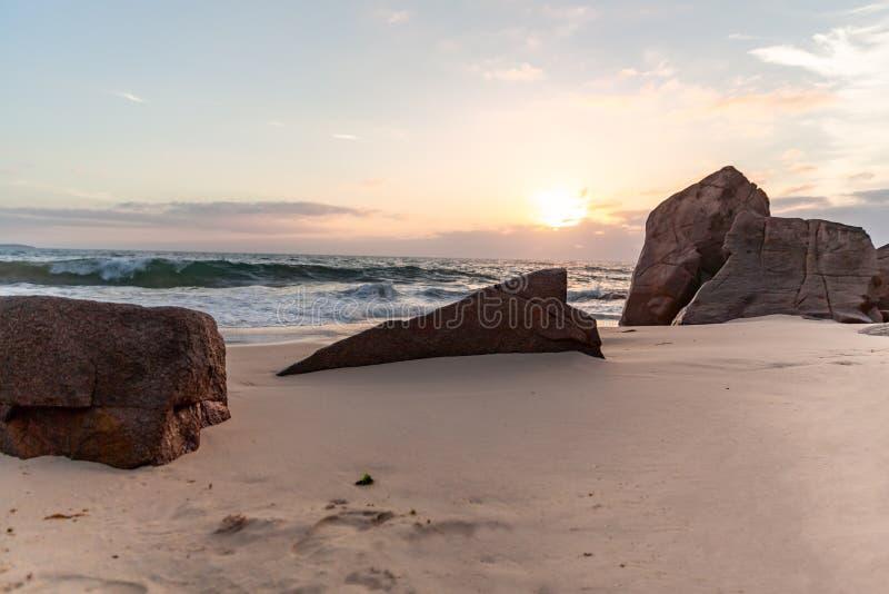 Soluppgång bland det härligt vaggar och havet royaltyfri foto