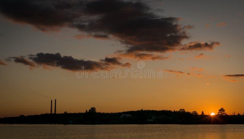 Soluppgång eller solnedgång nära en sjö med industriella lampglas arkivfoton