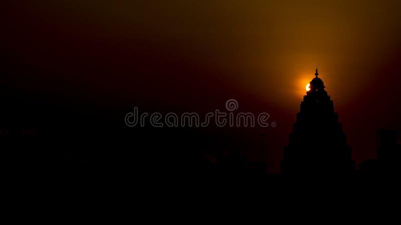 Soluppgång: Gloria bak överkanten av en hinduisk tempel arkivfoton