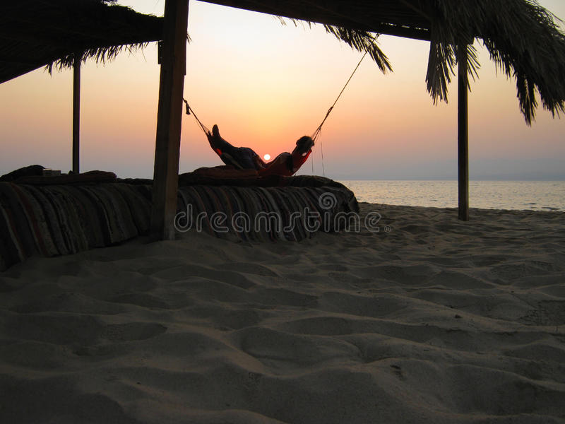 Soluppgång i en hängmatta på havet royaltyfria bilder