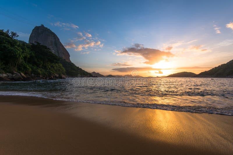 Soluppgång i stranden med det Sugarloaf berget royaltyfri foto