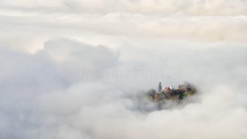 Soluppgång i Transylvaniaet County Rumänien med mist som täcker byn arkivbilder