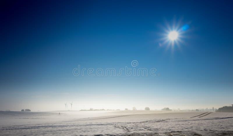Soluppgång i vinterunderland - solen skiner på en blå himmel arkivfoton