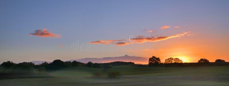 Soluppgång med glödande moln över ett brett lantligt landskap med mea arkivbilder