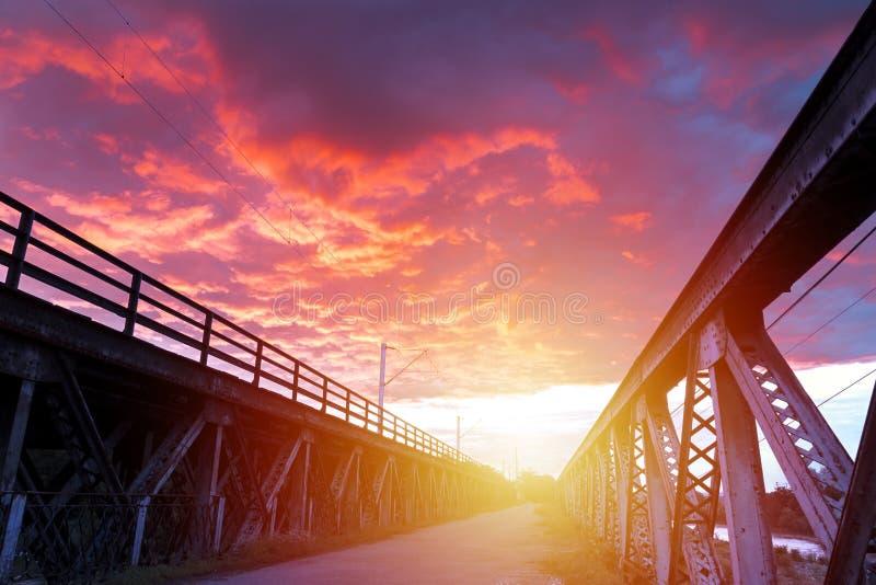 Soluppgång med spektakulär himmel över en gammal järnbro royaltyfri fotografi