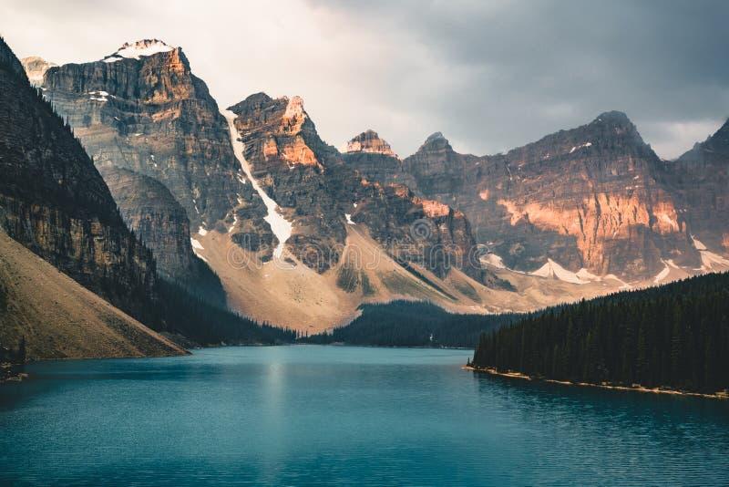 Soluppgång med turkosvatten av morän sjön med synd tände steniga berg i den Banff nationalparken av Kanada in arkivbild