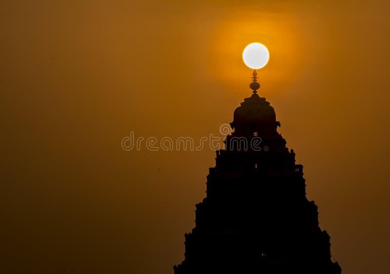 Soluppgång: Naturlig ljus garnering över en hinduisk tempel royaltyfria foton