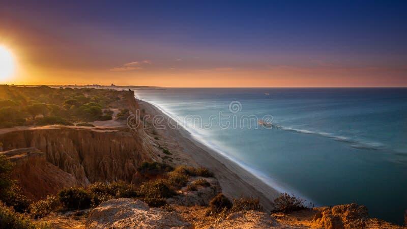 Soluppgång på Algarve strandklippor Portugal royaltyfri foto