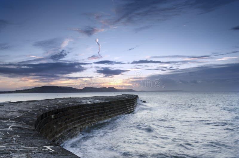Soluppgång på Cobben i Lyme Regis royaltyfri bild