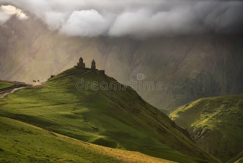 Soluppgång på den Gergeti Treenighetkyrkan med solstrålar av det Kazbegi berget i Georgia arkivbilder