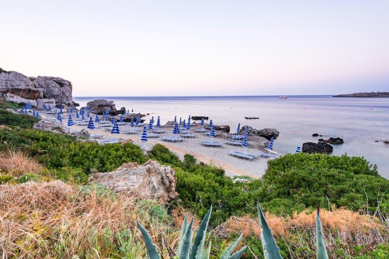 Soluppgång på den härliga stranden med paraplyer, Rhodes, Grekland royaltyfria bilder