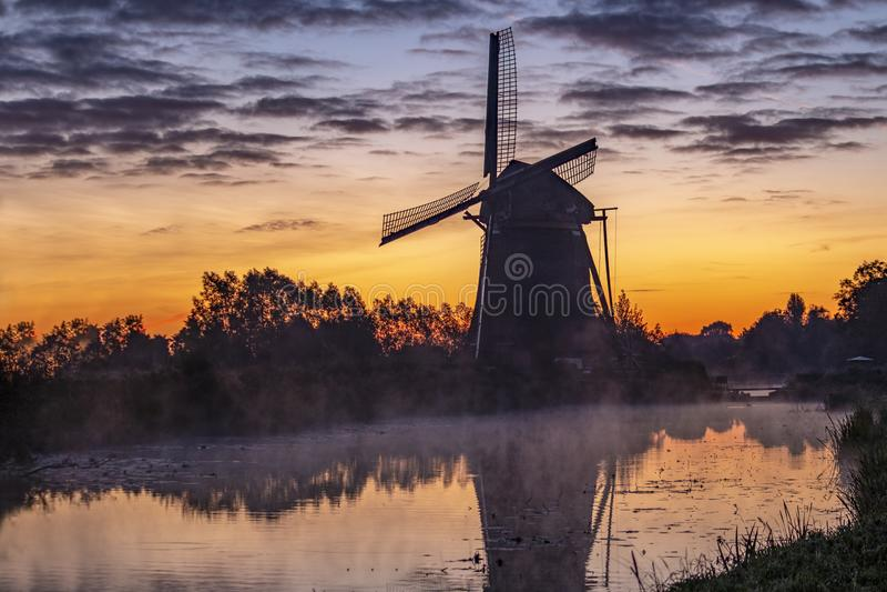 Soluppgång på den holländska väderkvarnen royaltyfri bild