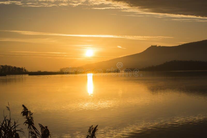 Soluppgång på en sjö i bakgrunden av PÃ-¡ lava royaltyfria bilder