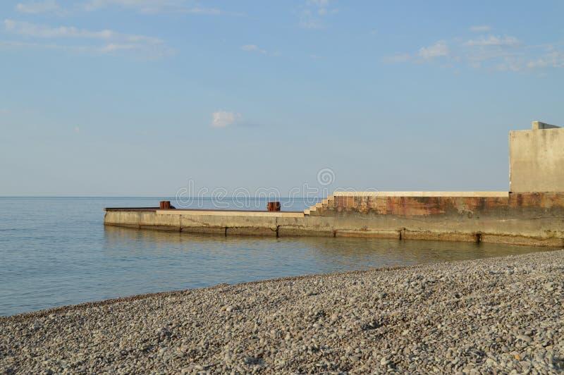 Soluppgång på havet, pir på kusten i ottan, stillhet, kopplar av royaltyfri fotografi