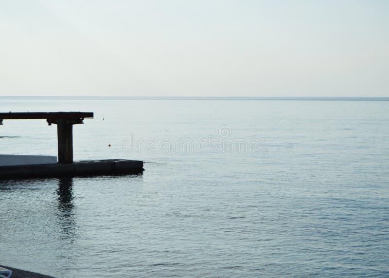 Soluppgång på havet, pir på kusten i ottan, stillhet, kopplar av arkivbilder