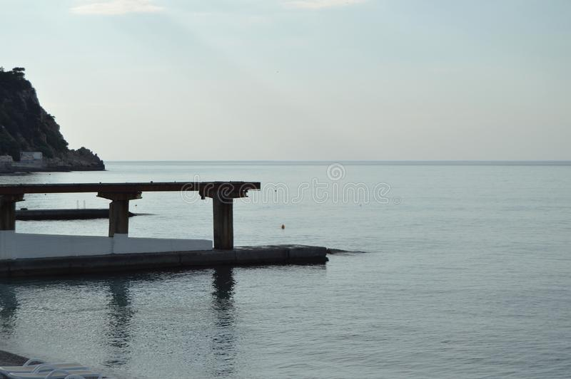 Soluppgång på havet, pir på kusten i ottan, stillhet, kopplar av royaltyfri bild