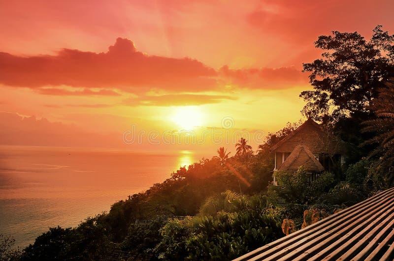 Soluppgång på havskusten i morgonen och hus i bergrommar royaltyfri bild