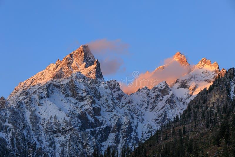 Soluppgång på snön korkade Tetons i nedgång fotografering för bildbyråer