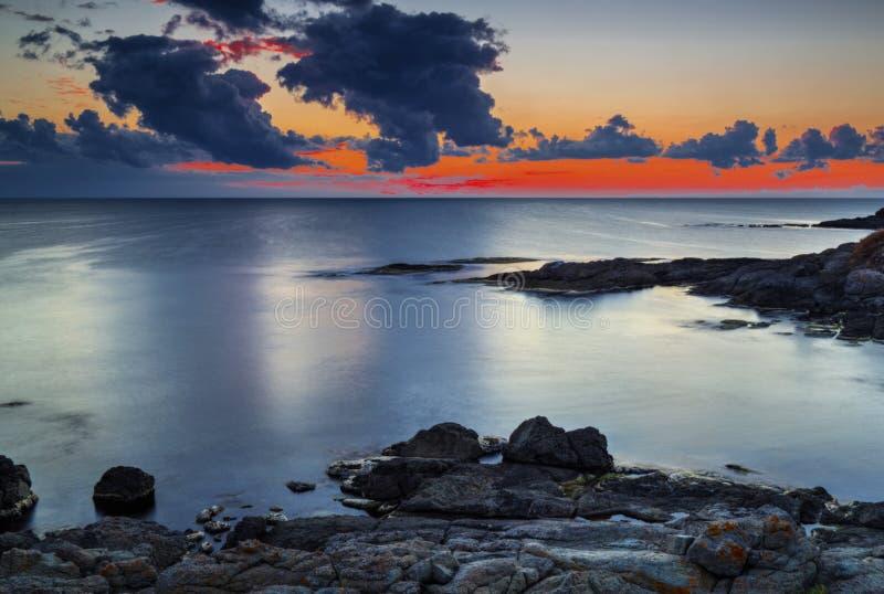 Soluppgång på stenig kust och dramatisk himmel fördunklar arkivfoto