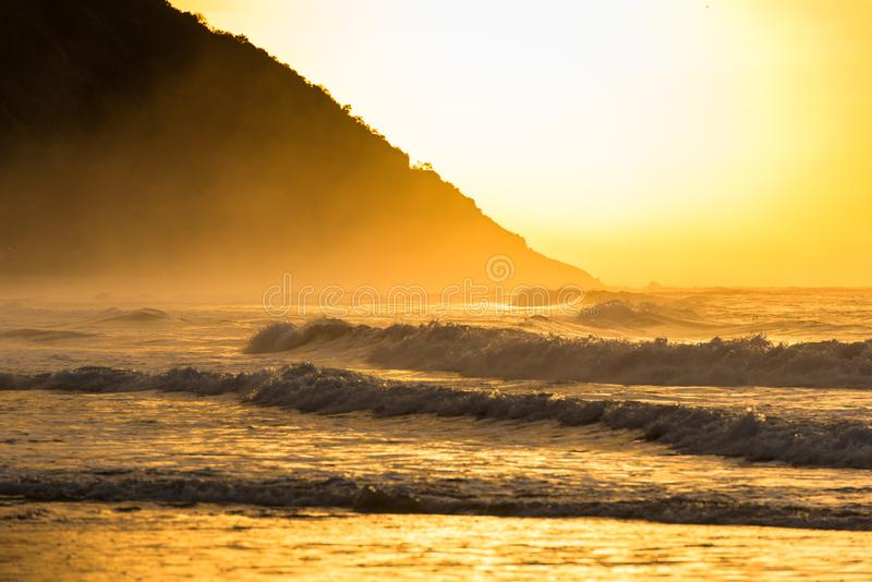 Soluppgång på stranden med bergkusten royaltyfria foton