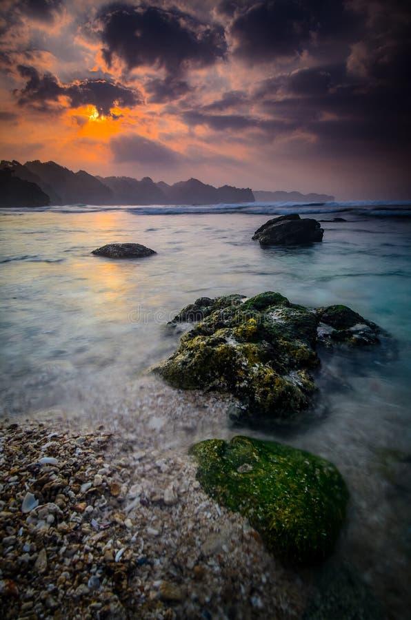 Soluppgång på stranden med den vita sand och reven fotografering för bildbyråer