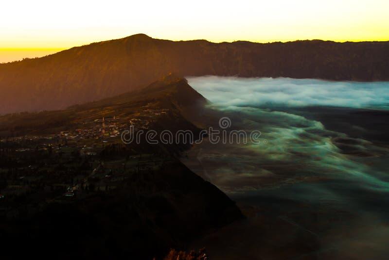 Soluppgång på vulkanmonteringen Bromo, sikt av den närliggande staden, tidigt arkivfoto