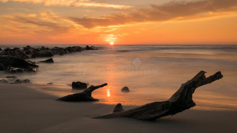 Soluppgång som ses från sanden, med lång exponering och havet som en spegel, stenar som kommer ut ur havet, och en journal som be royaltyfri foto