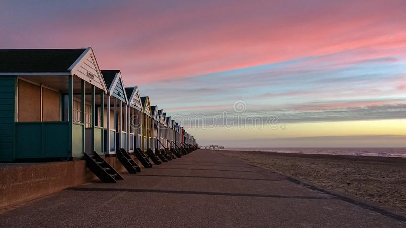 Soluppgång som skiner på färgglade strandkojor i Southwold, Suffolk, England arkivfoton