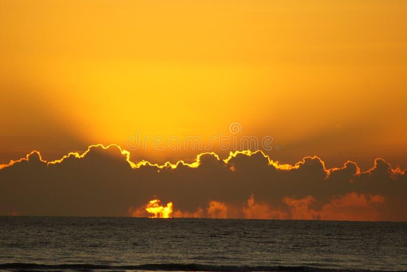 Soluppgång till och med moln över havet royaltyfri foto