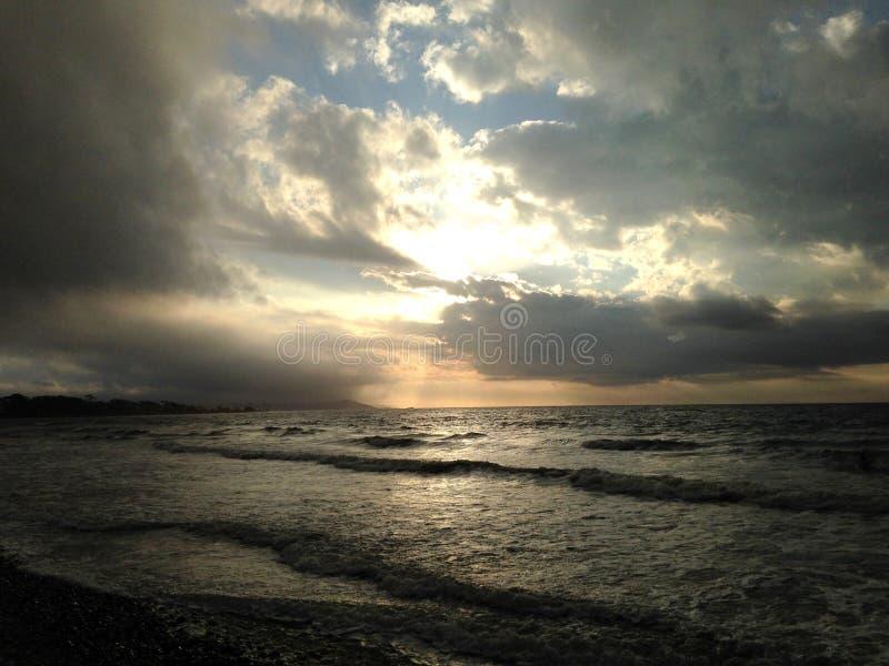 Soluppgång till och med moln över havet royaltyfri bild