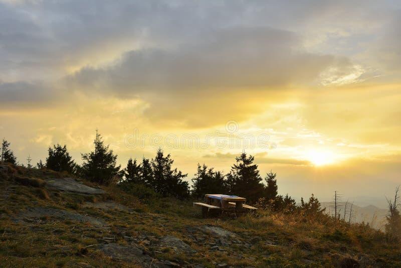 Soluppgången i bergen och trätabellen royaltyfria bilder