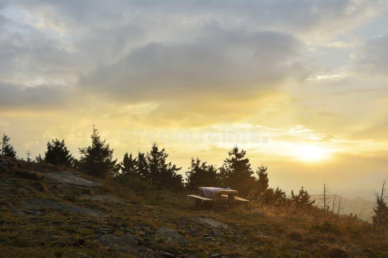 Soluppgången i bergen och trätabellen royaltyfri bild
